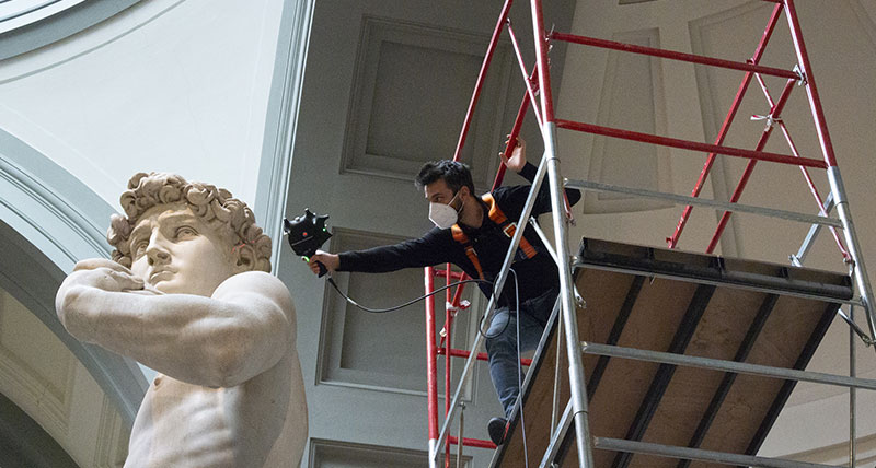 Michelangelo's David sculpture being scanned by a man on a scaffold platorm with a 3D laser scanner