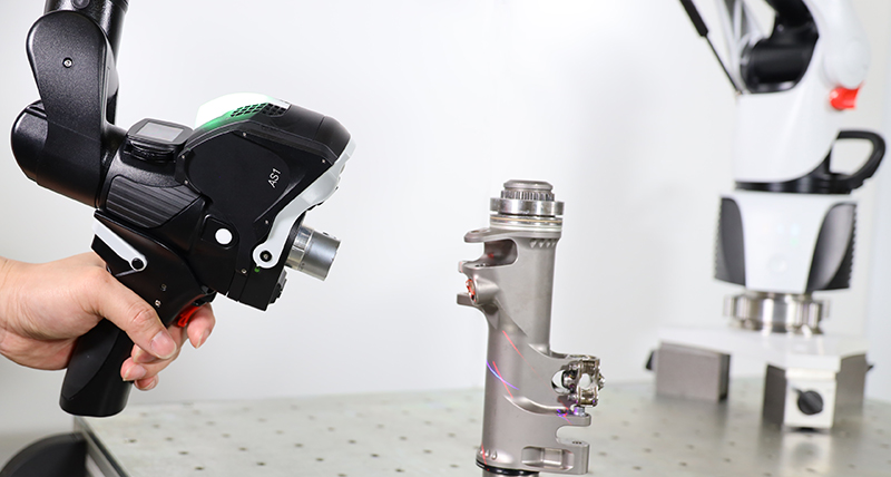 A 3d laser scanner inspecting a metal pipe object on a workbench the base of the portable measuring arm the scanner is mounted can be seen in the background