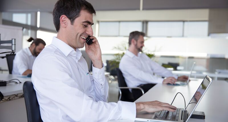 A customer support agent sat at a desk with a telephone to their ear and a laptop on a white desk.