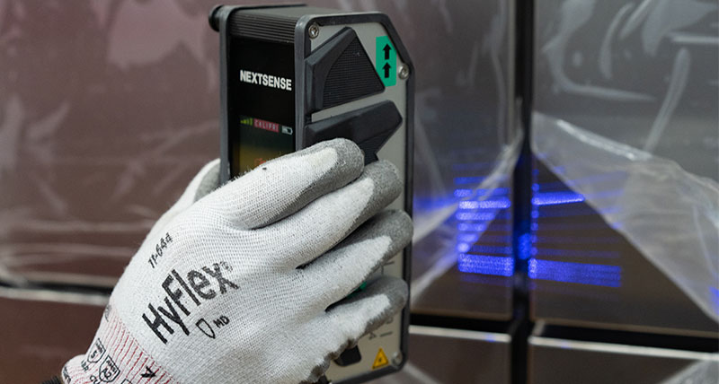 A close up of a gloved hand holding a profile and surface measuring device inspecting a gap