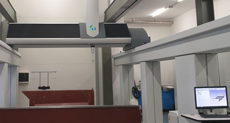 Gantry coordinate measuring machine inspecting a large steel part. PC-DMIS metrology software is also shown on a computer screen.